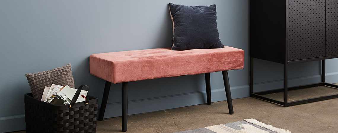 Bench in pink velour placed against the wall