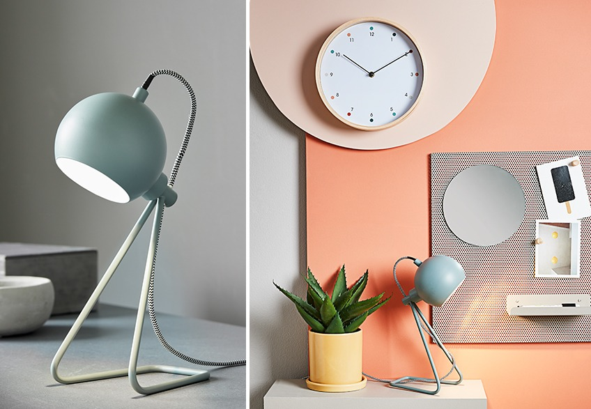 Green table lamp surrounded by wall clock, yellow plant pot and noticeboard with postcards