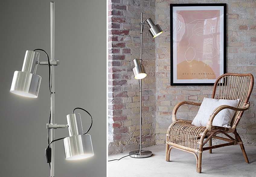 Floor lamp with two lights in a living room with poster in picture frame on the wall and armchair in rattan