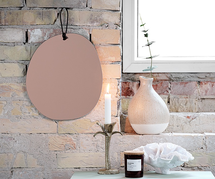 Wall mirror, candle stick, vase, scented candle and ornament by window