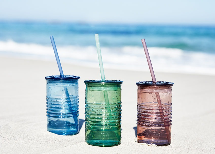 Three drinking cups in different colours in the sand on a beach