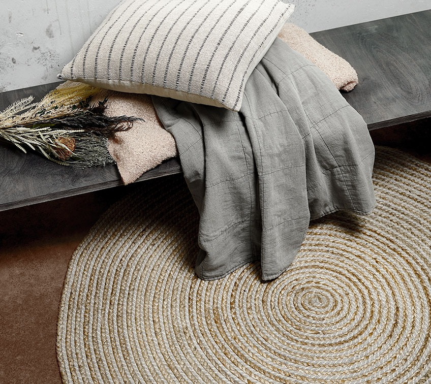 Circular rug in jute on the floor beneath a bench with a quilted blanket and a cushion