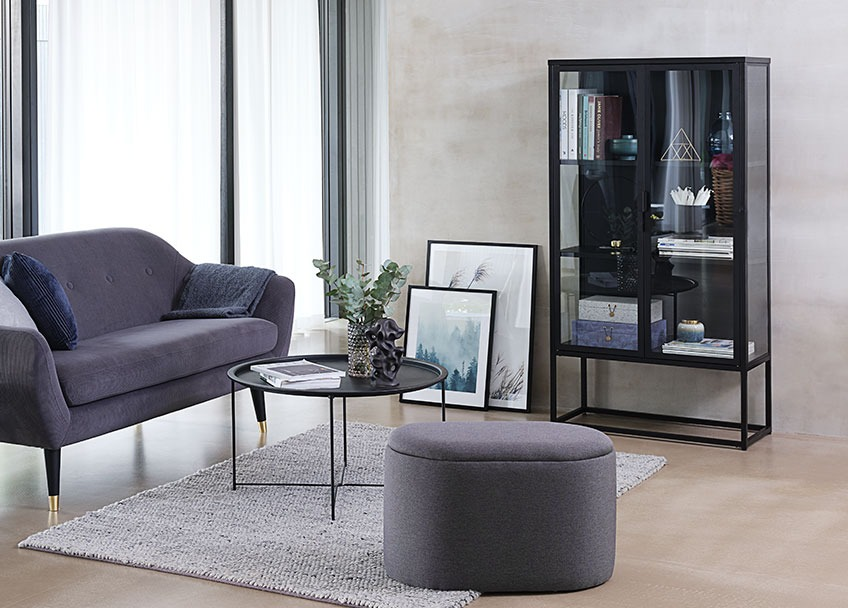 Oval pouffe in a living room with sofa, coffee table and a display cabinet