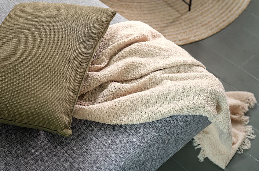 A green cushion and a knitted throw on a grey sofa