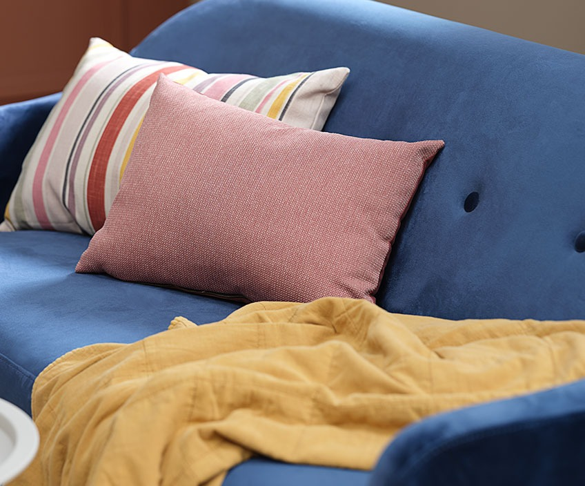 Colourful cushions and a quilted blanket in a blue sofa