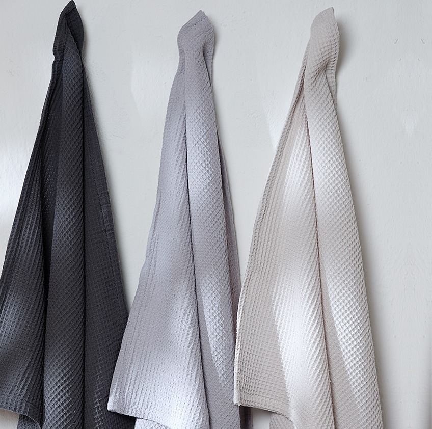 Tea towels in three different colours hanging on a wall