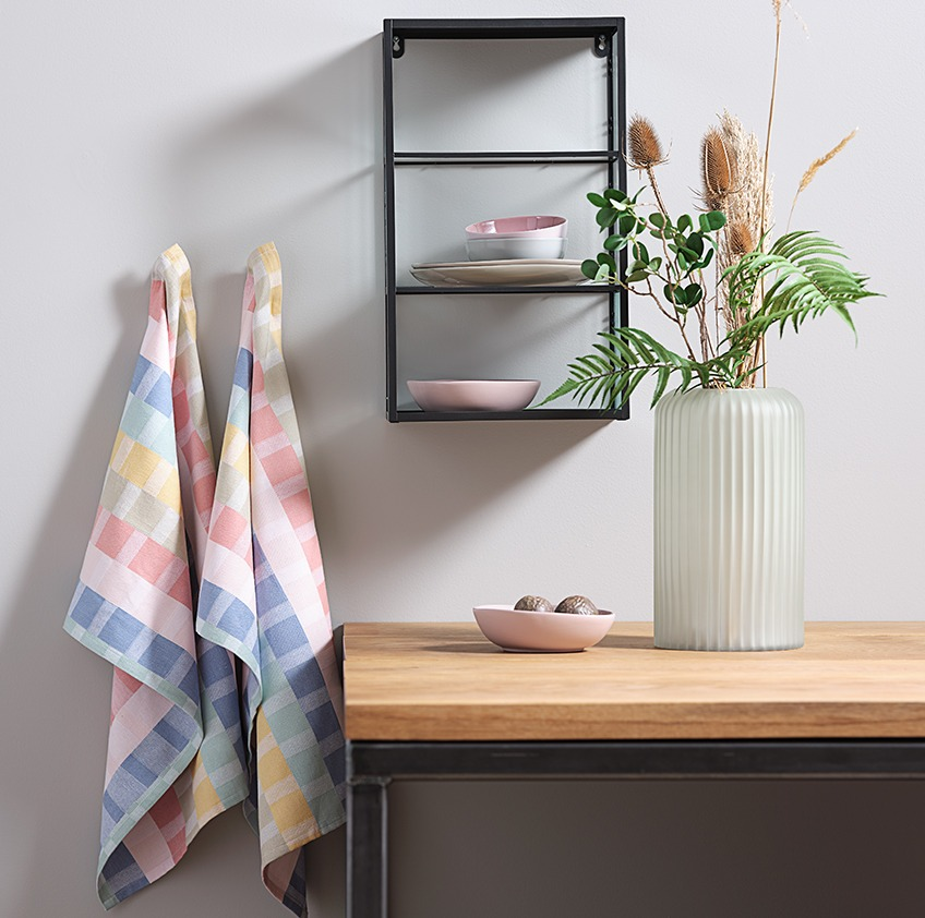 Cotton tea towels hanging next to a wall shelf and a vase on a table