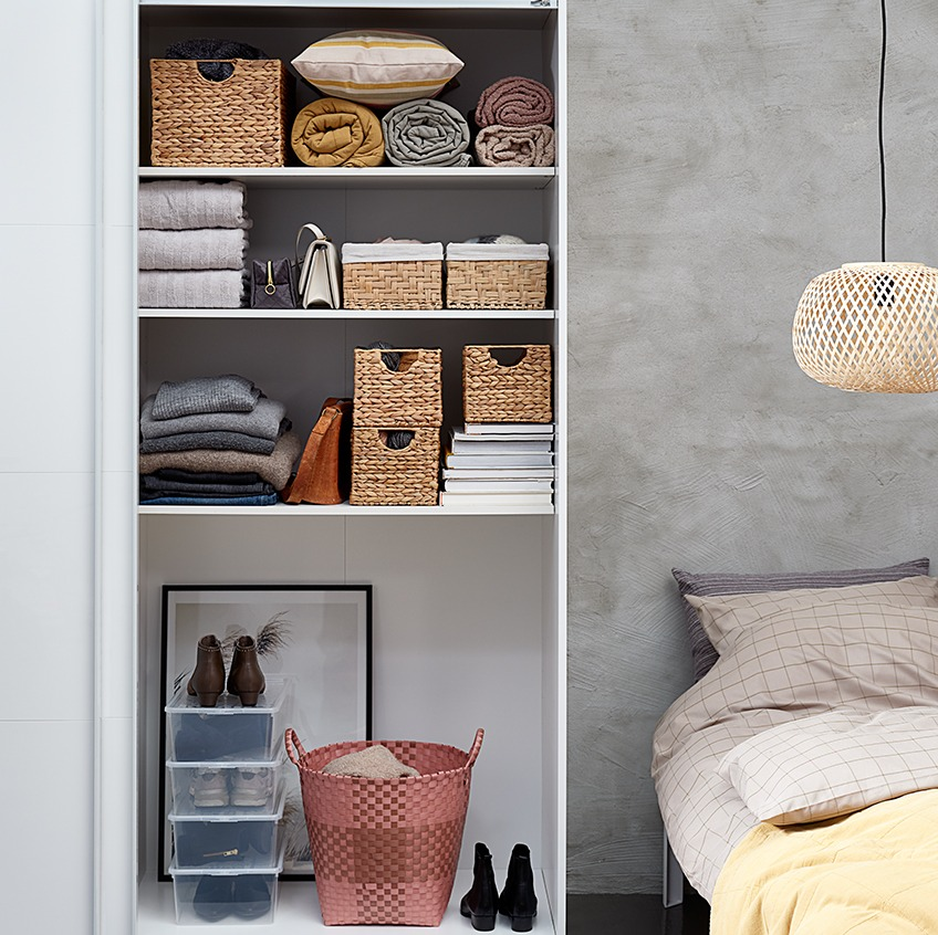 Bedroom with a tidy looking open wardrobe with baskets, stacks of towels and bags