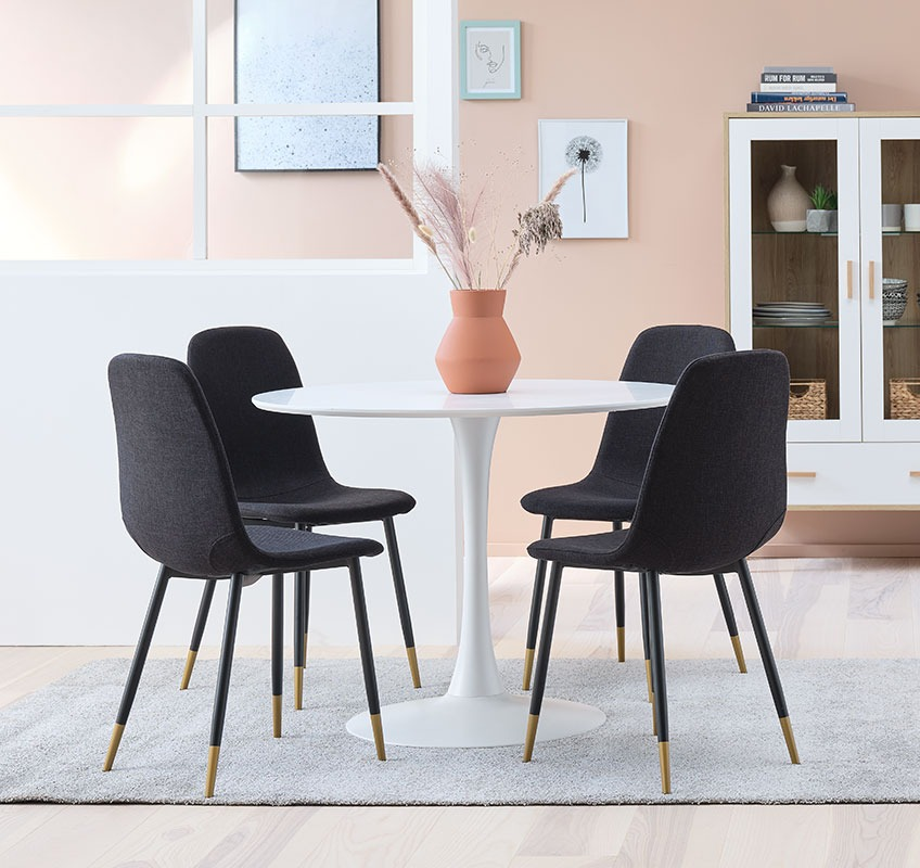 Modern dining chairs in black and gold around a white, round table